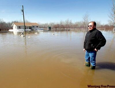 Keith Sinclair (above), Peguis First Nation's  assistant  emergency co-ordinator, stands in flood water from the Fisher River. Behind him, a  sandbag dike  protects Ron Spence's home.
