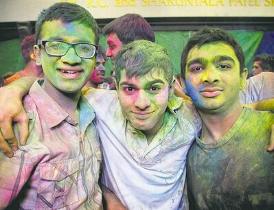 Harsh Patel (from left), Sagar Patel and Vismay Patel observe Holi at the Dr. Raj Pandey Hindu Centre Sunday. Holi, known as the festival of colours, marks the start of spring.