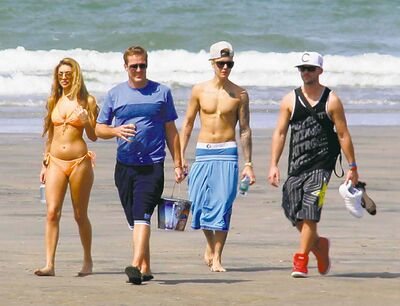 Justin Bieber (second right) and Chantel Jeffries (far left) walk with unidentified people on a beach in Punta Chame, Panama, Saturday.