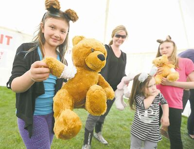 At top, nine-year-old Cadence Belbas shows of her bear Caramel's cast.