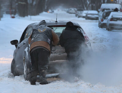 In a scene sure to play out again and again in coming days, two men on Thursday try to free a snowbound car on Aberdeen Avenue near Salter Street.