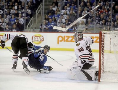 Chicago Blackhawks' Jan Rutta trips up Nikolaj Ehlers  in front of goaltender Cam Ward (30) whose stick goes flying after trying to knock the puck away during the second period Tuesday.