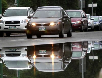 Traffic is reflected on Enfield Crescent Monday morning after overnight showers.