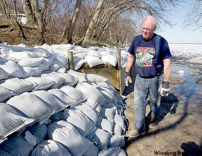 Larry Muirhead checks the sandbags at his home in Delta Beach.