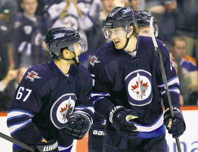 Jets Mark Scheifele (55) and Michael Frolik (67) celebrate Frolik's goal in the second period of Tuesday's pre-season NHL game.
