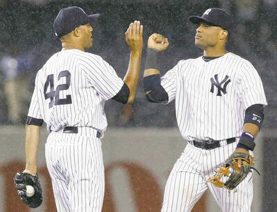 New York Yankees� Mariano Rivera (42) and Robinson Cano (24) celebrate after a baseball game against the Minnesota Twins on Friday, July 12, 2013, in New York. The Yankees won 2-0. (AP Photo/Frank Franklin II)