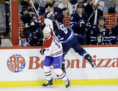 """JOHN WOODS / THE CANADIAN PRESS FILES</p> <p>Winnipeg Jets' Mathieu Perreault (85) is checked into boards by Montreal Canadiens' Brett Kulak (17) during first period NHL action in Winnipeg on Saturday, March 28, 2019.</p> <p>""""></a><figcaption readability="""