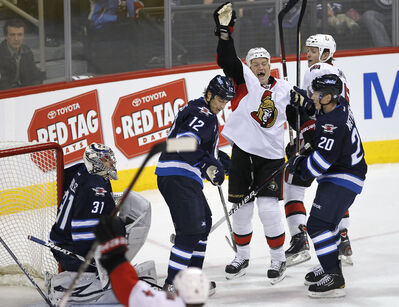 Ottawa Senators' Chris Neil (25) scores on Winnipeg Jets' goaltender Ondrej Pavelec during first-period NHL action at the MTS Centre Monday.