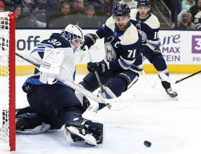 (AP Photo/Jay LaPrete)</p><p>Winnipeg Jets' Laurent Brossoit, left, makes a save against Columbus Blue Jackets' Nick Foligno during the second period Wednesday in Columbus, Ohio. </p>