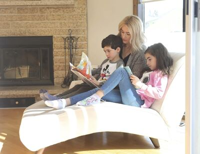 RUTH BONNEVILLE / WINNIPEG FREE PRESS FILES</p><p>With schools closed during the pandemic, Catherine DeMarco reads in their Winnipeg home with her son, Cristiano, and daughter, Gia.</p>