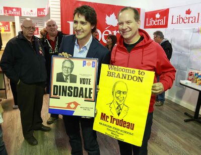 Federal Liberal leader Justin Trudeau and local candidate Rolf Dinsdale pose with old posters of their politician fathers.