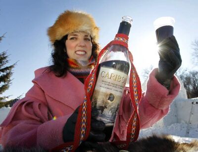 Ginette Lavack Walters, executive director of Festival du Voyageur, holds up a bottle of potent Caribou, which attendees can sample until Feb. 26.