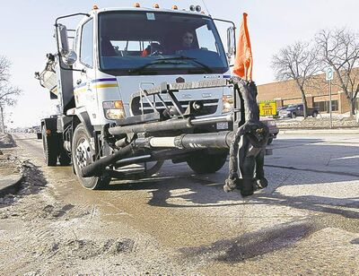 Pothole patchers repair a rough stretch on King Edward Street at Logan Avenue.