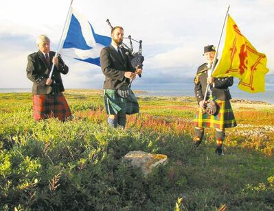 Mark Ingebrigtson (left) holds the Scottish flag with the Cross of St. Andrew with piper Joshua Krozhan and Rob Bruce-Barron.