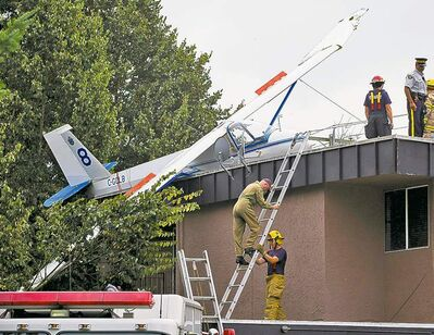 Firefighters and an RCMP officer stand on the roof of an apartment building and convenience store where a glider crashed in Langley, B.C., on Sunday. An air cadet was on a training exercise at the time of the crash. The pilot, whose age was not released, survived. Transport Canada will investigate the incident.
