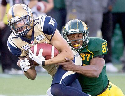 Winnipeg Blue Bombers Nick Moore (17) is tackled by Edmonton Eskimos Otha Foster (37) during second half action in Edmonton, Alta., on Monday.