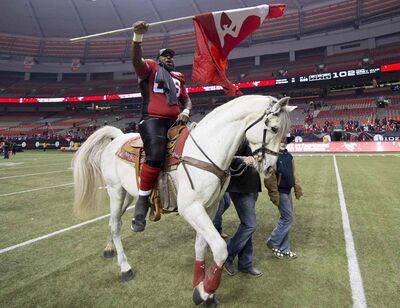 Stanley Bryant celebrates his teams win against the Hamilton Tiger-Cats by riding a horse following the 102nd Grey Cup in Vancouver.