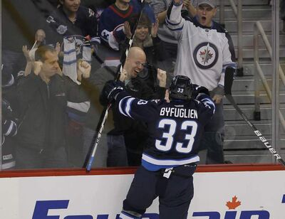 Winnipeg Jets' Dustin Byfuglien (33) pounds on the glass after scoring against the Philadelphia Flyers' during first period NHL action on Tuesday.