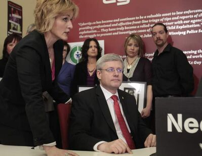 Prime Minister Stephen Harper with Signy Arnason, director of Cybertip.ca, surrounded by family of victims of cyber-bulyling at the Canadian Centre For Child Protection.