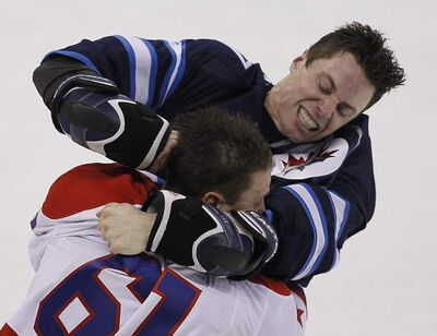 Winnipeg Jets forward James Wright and Washington Capitals' Steve Oleksy fight during the first-period in Winnipeg.