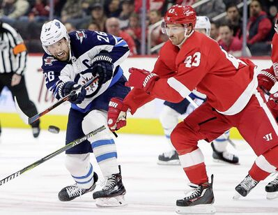 Winnipeg Jets right wing Blake Wheeler shoots the puck against Detroit Red Wings centre Darren Helm during the first period Friday in Detroit.