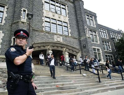 A Toronto police officer in front of Central Technical School in Toronto in 2010. In 2017 the Toronto District School Board voted to axe its decade-old, onsite police program. THE CANADIAN PRESS/Nathan Denette</p>