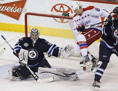 Washington Capitals' Matt Hendricks (26) jumps in the air as Winnipeg Jets goaltender Ondrej Pavelec (31) stops the Capitals' shot during first-period NHL action in Winnipeg on Friday.