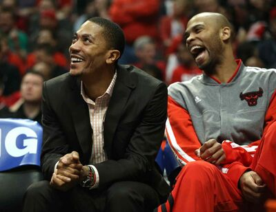 The Chicago Bulls' Derrick Rose, left, and Taj Gibson laugh on the bench, during the first half against the Brooklyn Nets on Saturday, April 27, 2013, in Game 4 of the Eastern Conference Playoffs first-round series at the United Center in Chicago, Illinois. Chicago won in triple overtime, 142-134.
