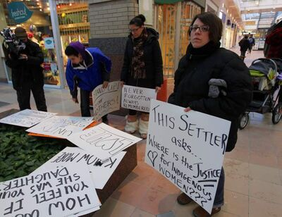 Participants prepare signs at Portage Place mall before marching to remember missing and murdered women.