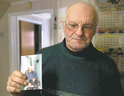 Ryan Remiorz / THE CANADIAN PRESSJean-Andre Michaud holds a photo of his father, Paul-Etienne Michaud who died in the seniors� residence fire in L�Isle-Verte, Que. Some in the town have blamed the elder Michaud�s smoking for starting the blaze.