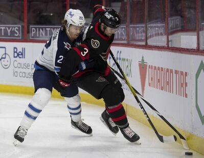 Winnipeg Jets centre Mason Appleton battles with Ottawa Senators defenceman Josh Brown along the boards during the first period Thursday in Ottawa. THE CANADIAN PRESS/Adrian Wyld