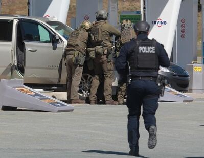 RCMP officers prepare to take a person into custody at a gas station in Enfield, N.S. on Sunday April 19, 2020. A suspect in an active shooter investigation is in custody in Nova Scotia, with police saying several people were harmed before a man wearing police clothing was arrested. Gabriel Wortman was arrested by the RCMP at the Irving Big Stop in Enfield, N.S., about 35 km from downtown Halifax. THE CANADIAN PRESS/Tim Krochak