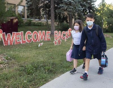 Adrien, 7, left, and Damien, 10, Borgia arrive for the first day of school in Montreal, Tuesday, Aug. 31, 2021, as the COVID-19 pandemic continues in Canada and around the world. THE CANADIAN PRESS/Graham Hughes