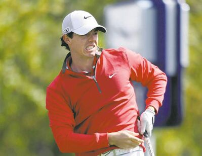 It's not as bad as the grimace lets on: Rory McIlroy, reacting to a drive on the first hole, is four shots back.