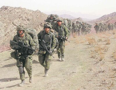Canadian soldiers hike with their packs through the mountains of eastern Afghanistan in 2002.