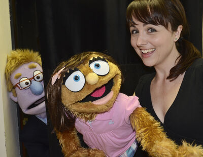 Paula Potosky with her character, Kate Monster, as the Trekkie Monster puppet peers around the corner.