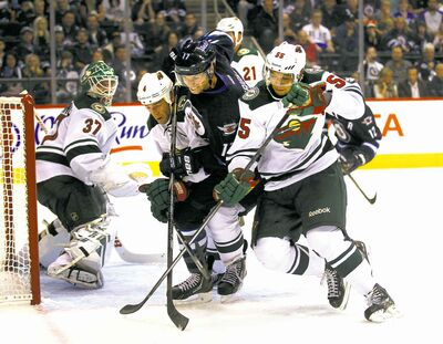 The Jets' James Wright is sandwiched by the Minnesota Wild's Clayton Stoner (left) and Erik Haula in front of the Wild net in second-period action Thursday.