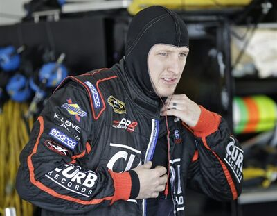 Michael McDowell puts on his fire suit during a practice session for the NASCAR Sprint Cup Series Daytona 500 auto race Friday, Feb. 22, 2013, at the Daytona International Speedway in Daytona Beach, Fla. (AP Photo/Chris O'Meara)