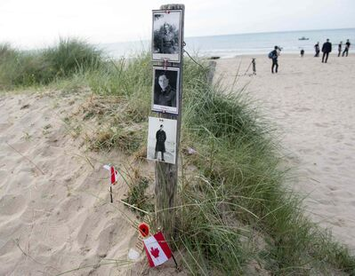 A beach post has photo's of Canadian soldiers pinned to it on Juno Beach following a ceremony of rememberance in Courcelles-sur-mer, France, Friday June 6, 2014.