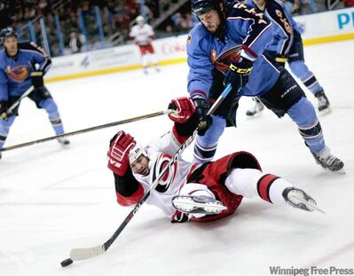 Carolina Hurricanes Chad LaRose  falls down in front of Atlanta Thrashers Zach Bogosian during the third period of a game  Feb. 13, 2011 in Atlanta.