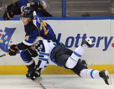 Jets defenceman Toby Enstrom falls headfirst into the Blues' T.J. Oshie during their game in St. Louis last night.