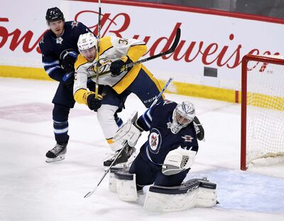 Winnipeg Jets' goaltender Connor Hellebuyck (37) makes a save as Nashville Predators' Yakov Trenin (32) looks for the rebound in front of Dmitry Kulikov (7) during first period NHL action in Winnipeg on Sunday Jan. 12, 2020. (Fred Greenslade / The Canadian Press)</p>