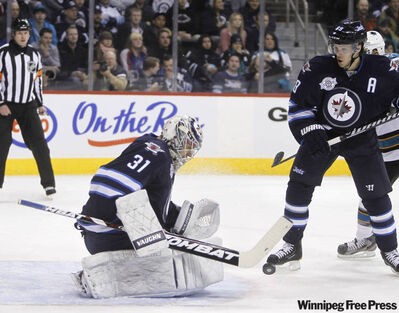 Winnipeg Jets' goaltender Ondrej Pavelec (31) makes a save late in the first period against the San Jose Sharks Thursday.