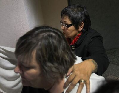 Delores Chief Abigosis (rear) leaves the Phoenix Sinclair inquiry for a lunch break Monday while her advocate tries to block her face from the media.