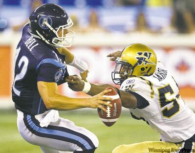 Frank Gunn / the canadian pressToronto Argonauts quarterback Dalton Bell comes under pressure from the Blue Bombers� Kenny Mainor during first-half action in Toronto Saturday afternoon.