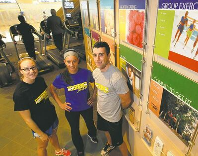 Certified personal trainers (R-L) Tim Shantz, Alex Nataluk and Ashley Derlago by a program board at the Wellness Institute.