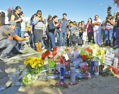 People gather at a roadside memorial for actor Paul Walker in Valencia, Calif. Walker was a passenger in the car that crashed and burned on Saturday, as a charity event at a nearby car shop was winding down.