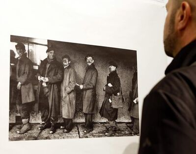 "FILE - In this Jan. 28, 2016 file photo, a man looks at a photograph by Robert Frank at the opening of the exhibition featuring Frank's work, ""Robert Frank: Books and Films, 1947–2016,"" at New York University's Tisch School of the Arts in New York. Frank, one of the 20th century's greatest photographers, has died at age 94. Frank died Monday, Sept. 9, 2019, in Inverness, on Cape Breton Island in Nova Scotia, where he had a summer home, The New York Times reports. (AP Photo/Kathy Willens, File)"