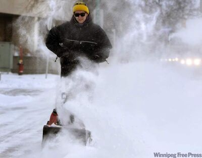 Jonathan Williams clears snow off the sidewalk at the Canadian Red Cross building on Portage Avenue on Friday morning.