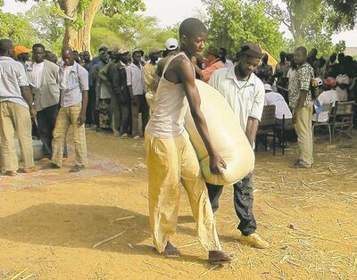 Gourma villagers carry a 100-kilogram bag of millet from a Nigerien food-distribution depot (above) near the border with Burkina Faso. Millet (left) is the staple of the diet.